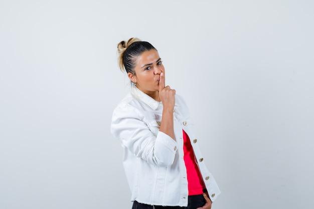 Jeune femme en t-shirt, veste blanche montrant un geste de silence et l'air confiant, vue de face.