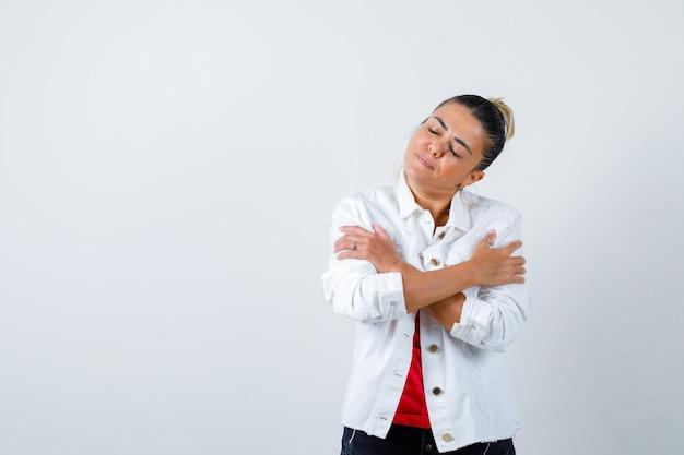 Jeune femme en t-shirt, veste blanche se serrant dans ses bras et semblant paisible, vue de face.