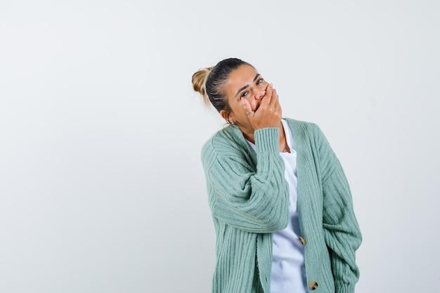 Jeune femme en t-shirt, veste couvrant la bouche avec la main et l'air heureux