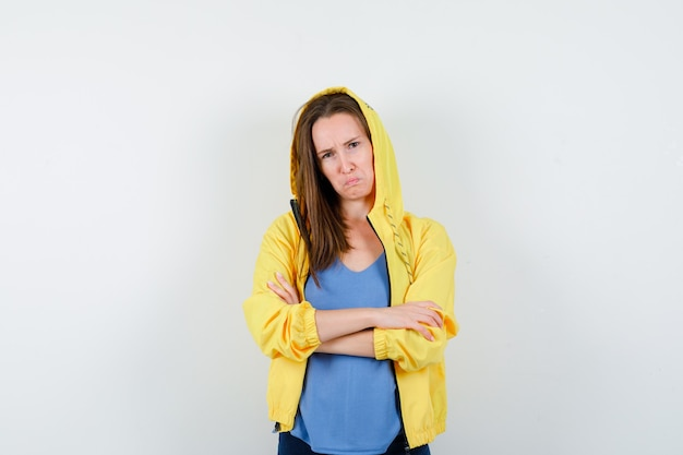 Jeune femme en t-shirt, veste debout avec les bras croisés et l'air bouleversé, vue de face.