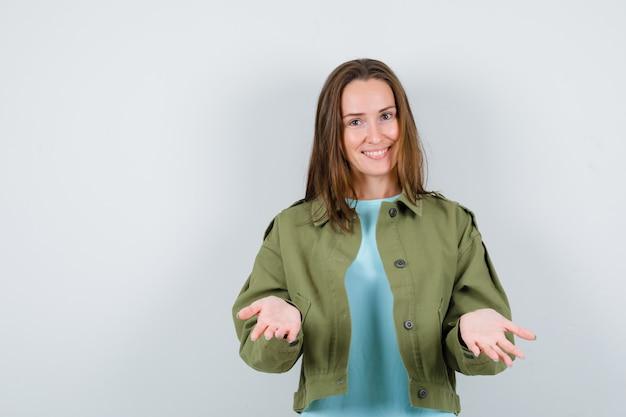 Jeune femme en t-shirt, veste étalée sur les paumes, regardant la caméra et l'air heureux, vue de face.