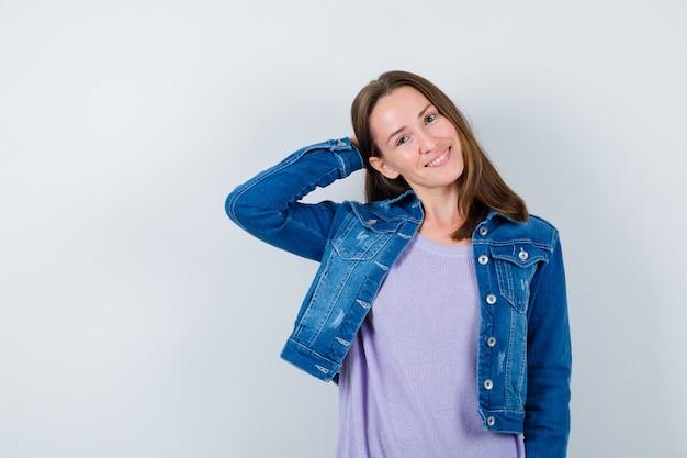 Jeune femme en t-shirt, veste en jean gardant la main derrière la tête et l'air joyeux, vue de face.