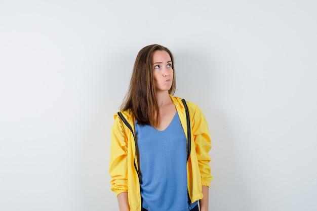 Jeune femme en t-shirt, veste en levant et regardant réfléchie, vue de face.