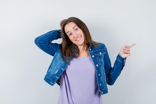 Jeune femme en t-shirt, veste avec la main derrière la tête, pointant vers la droite et l'air indécis, vue de face.