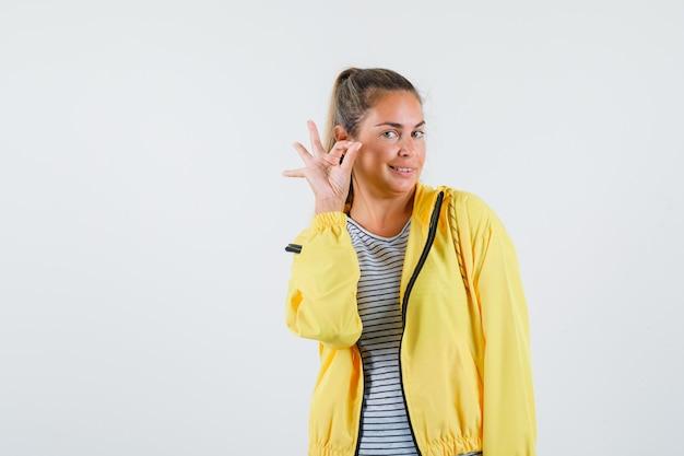 Jeune femme en t-shirt, veste montrant le geste ok et à la vue de face, confiant.