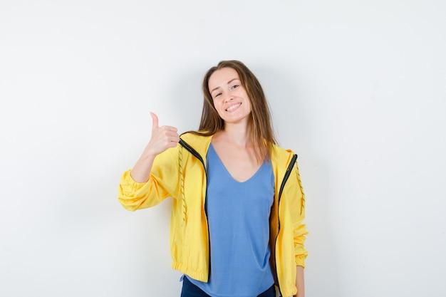 Jeune femme en t-shirt, veste montrant le pouce vers le haut et l'air confiant, vue de face.