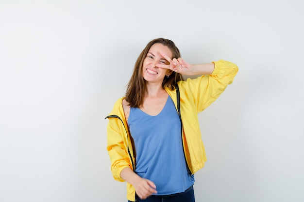 Jeune femme en t-shirt, veste montrant le signe v sur l'œil et l'air confiant, vue de face.