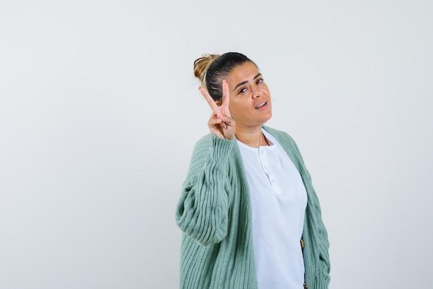 Jeune femme en t-shirt, veste montrant le signe de la victoire et semblant chanceuse