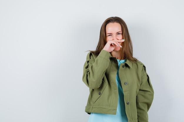 Jeune femme en t-shirt, veste pinçant le nez à cause d'une mauvaise odeur et ayant l'air dégoûtée, vue de face.