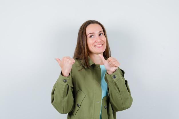 Jeune femme en t-shirt, veste pointant de côté avec les pouces et à la gaieté, vue de face.