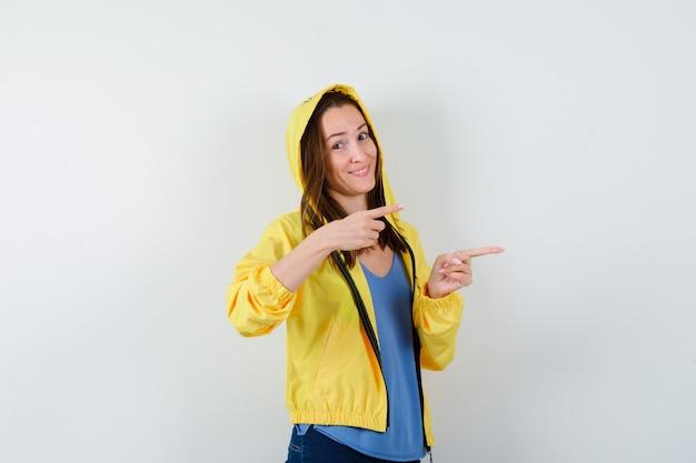 Jeune femme en t-shirt, veste pointant vers le côté droit et semblant confiante, vue de face.