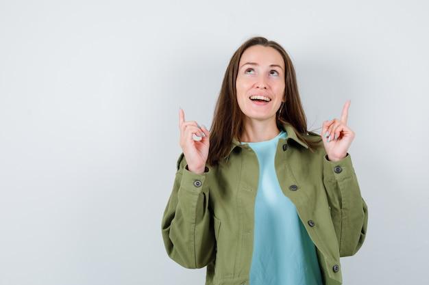 Jeune femme en t-shirt, veste pointant vers le haut, regardant vers le haut et semblant joyeuse, vue de face.