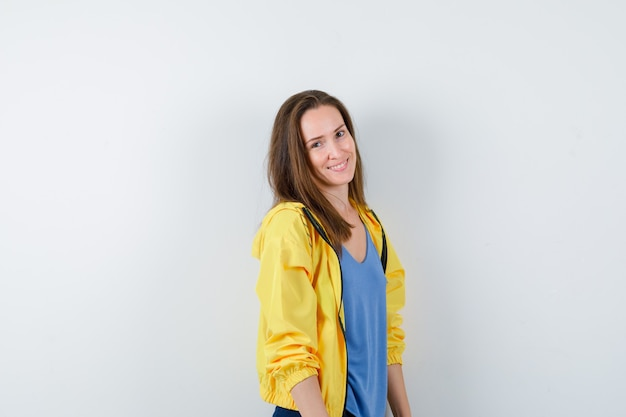 Jeune Femme En T-shirt, Veste Regardant La Caméra Et Charmante, Vue De Face. Photo gratuit