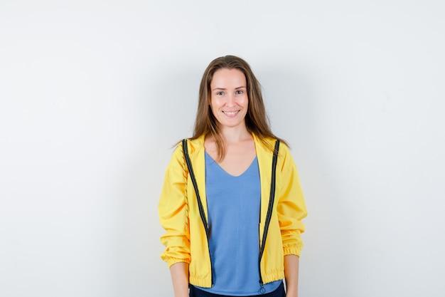 Jeune femme en t-shirt, veste regardant la caméra et semblant joyeuse, vue de face.