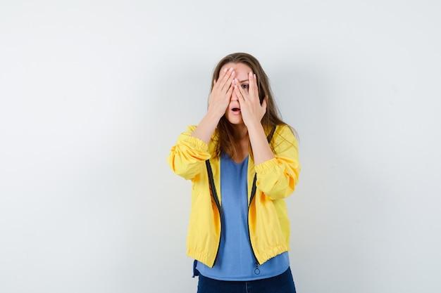 Jeune femme en t-shirt, veste regardant à travers les doigts et ayant l'air effrayée, vue de face.