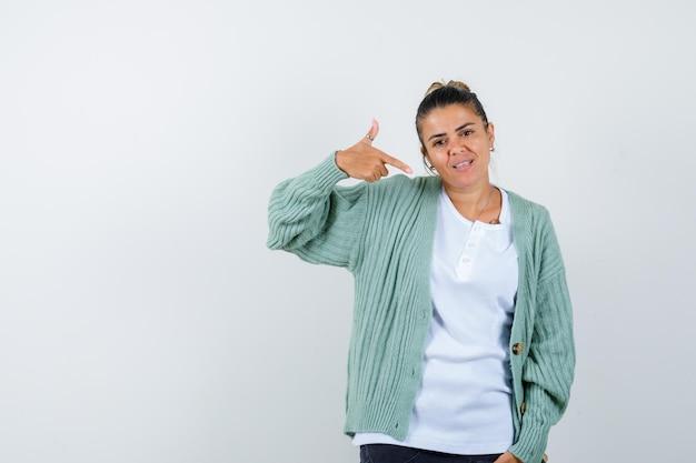 Jeune femme en t-shirt, veste se pointant et semblant fière