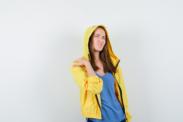 Jeune femme en t-shirt, veste souffrant de douleurs à l'épaule et à l'aise, vue de face.
