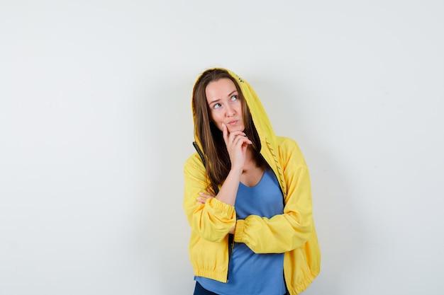 Jeune femme en t-shirt, veste soutenant le menton à portée de main et semblant rêveuse