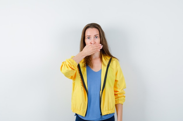 Jeune femme en t-shirt, veste tenant la main sur la bouche et l'air choqué, vue de face.