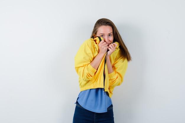 Jeune femme en t-shirt, veste tirant le col sur le visage et ayant l'air effrayée, vue de face.