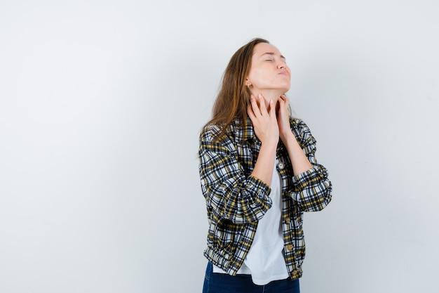 Jeune femme en t-shirt, veste touchant la peau de son cou et à la vue fatiguée, de face.