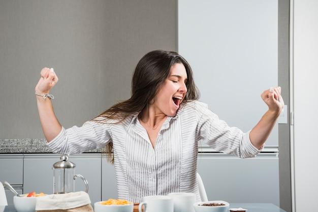 Jeune femme, à, table petit déjeuner, bâiller, et, s'étendant mains
