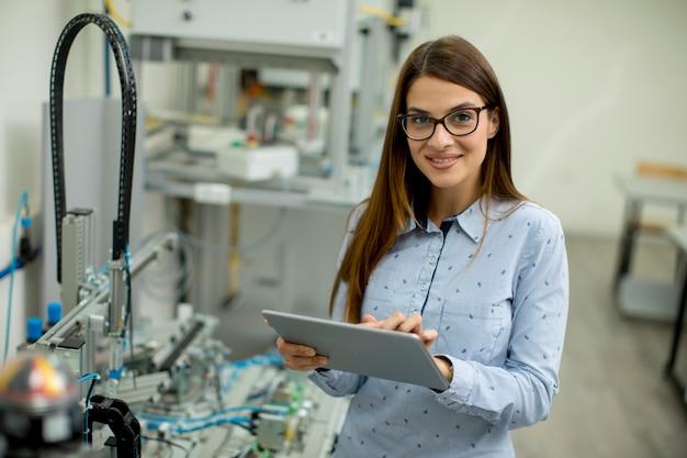 Jeune femme avec tablette numérique dans l'atelier de l'électronique