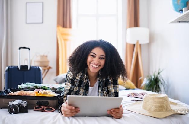 Jeune femme avec tablette et valise d'emballage pour des vacances à la maison, regardant la caméra.