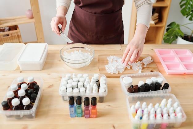 Jeune femme en tablier brun prenant morceau de masse coupée de planche de bois pour le mettre dans un bol en cours de fabrication de savon