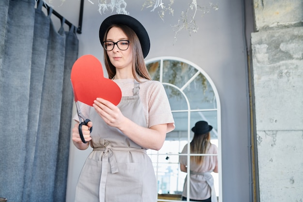 Jeune femme en tablier et chapeau tenant grand coeur de papier rouge et ciseaux tout en se préparant pour la saint-valentin