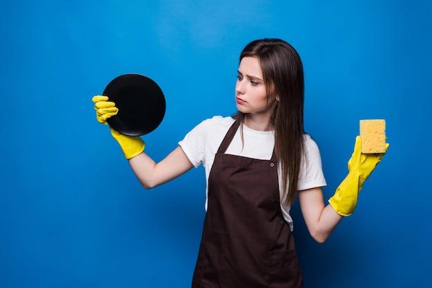 Jeune femme en tablier avec éponge à la recherche de plat lavé. vaisselle propre, l'ordre dans la maison demande beaucoup de travail. une femme au foyer parfaite mérite le rang