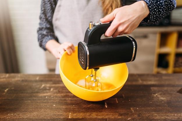 Jeune femme en tablier fouetter la pâte dans un bol avec mélangeur