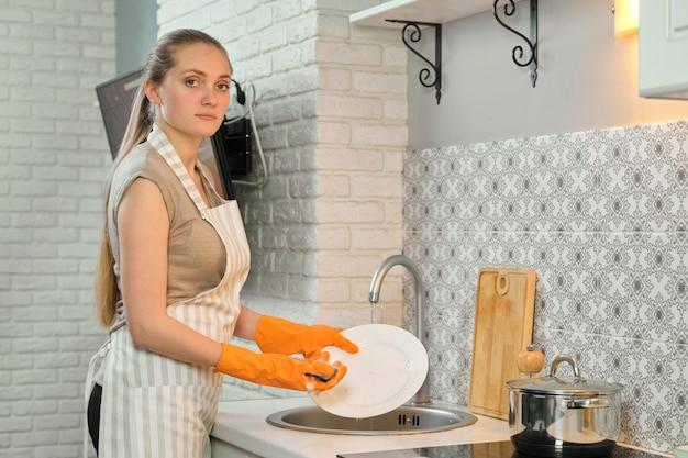 Jeune, femme, tablier, gants, lavage, vaisselle, éponge, détergent