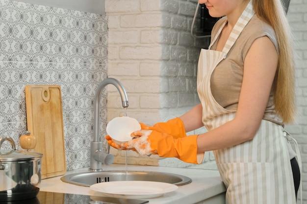 Jeune femme en tablier gants laver la vaisselle avec une éponge et un détergent