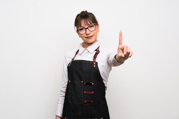 Jeune femme avec tablier montrant et en levant un doigt