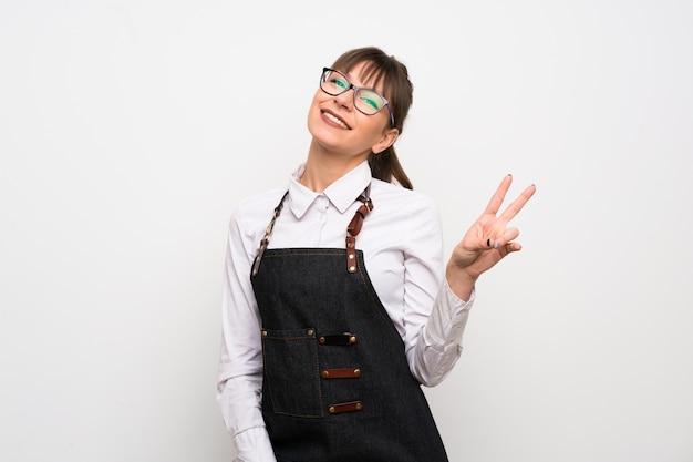 Jeune femme avec tablier souriant et montrant le signe de la victoire
