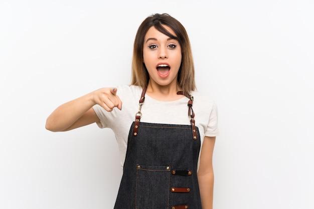 Jeune femme avec un tablier surpris et pointant devant