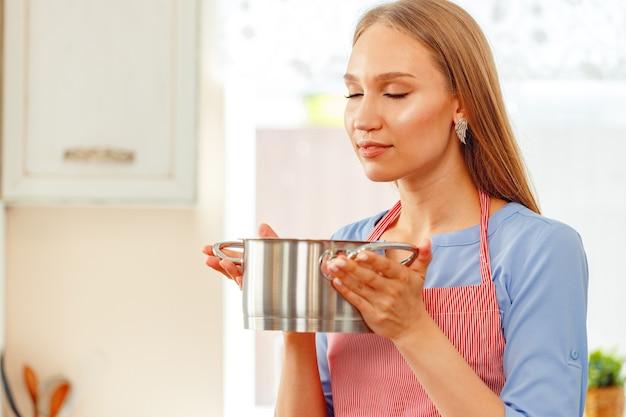 Jeune femme en tablier tenant un pot en métal avec un plat cuisiné
