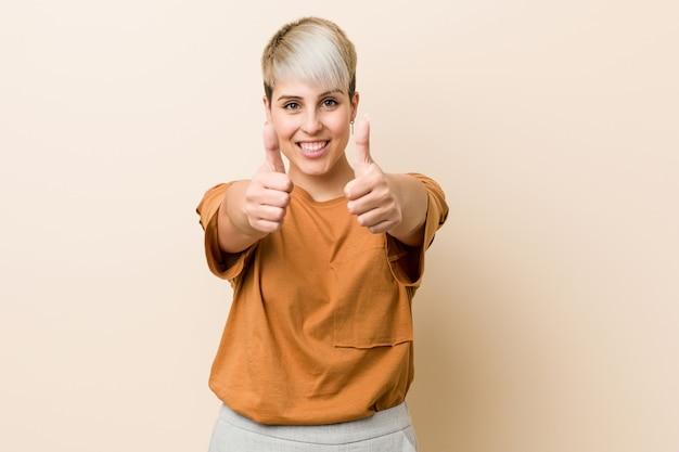 Jeune femme de taille plus aux cheveux courts avec le pouce levé, applaudit à quelque chose, soutient et respecte le concept.