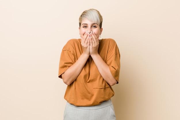 Jeune femme de taille plus aux cheveux courts qui rit, qui se couvre la bouche avec les mains.