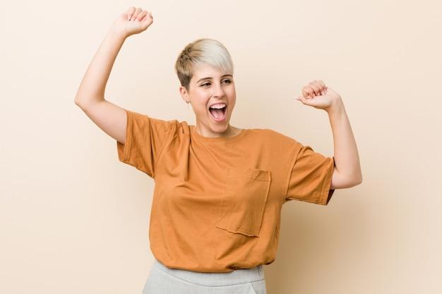 Jeune femme de taille plus avec les cheveux courts célébrant une journée spéciale, saute et lève les bras avec énergie.