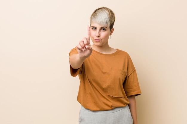Jeune femme de taille plus avec les cheveux courts, montrant le numéro un avec le doigt.