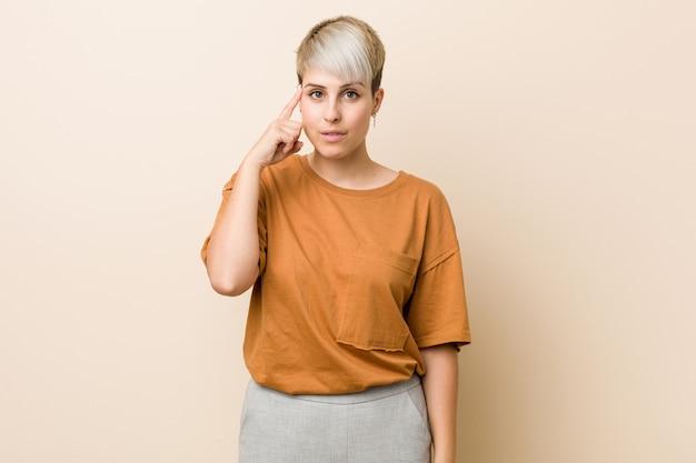 Jeune femme de taille plus avec les cheveux courts, pointant le temple avec le doigt, pensant, concentrée sur une tâche.