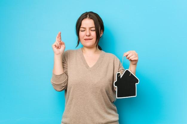 Jeune femme de taille plus courbée tenant une icône d'accueil croisant les doigts pour avoir de la chance