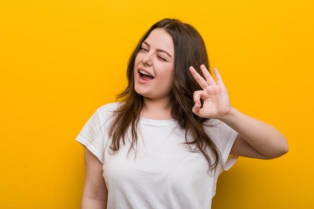 Jeune femme de taille plus galbée cligne de l'oeil et détient un geste correct avec la main.