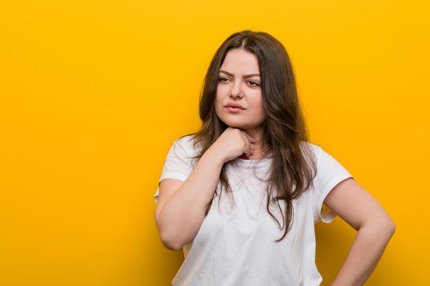 Une jeune femme de taille plus galbée a mal à la gorge à cause d'un virus ou d'une infection.