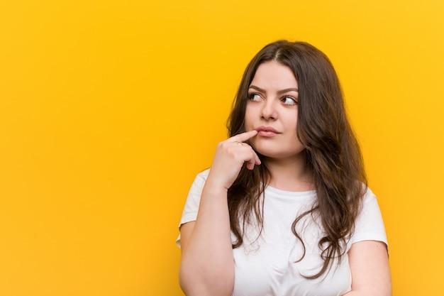 Jeune femme de taille plus galbée regardant de côté avec une expression douteuse et sceptique.