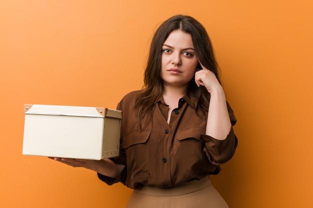 Jeune femme de taille plus galbée tenant une boîte pointant sa tempe avec le doigt, pensant, concentrée sur une tâche.