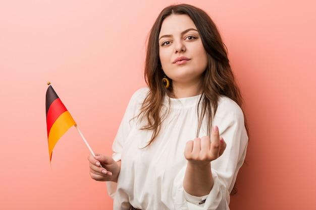 Jeune femme de taille plus galbée tenant un drapeau allemand pointant du doigt vers vous, comme si elle s'invitait.