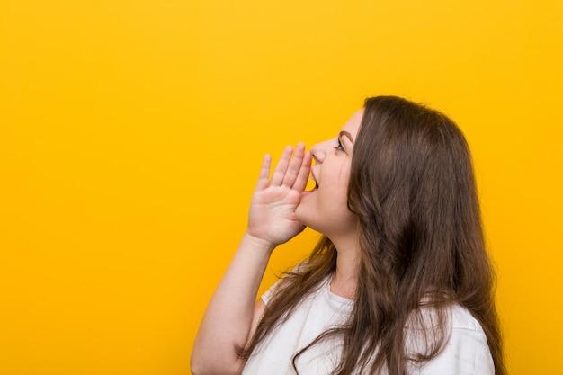 Jeune femme de taille plus sinueuse criant et tenant la paume près de la bouche ouverte.